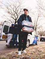 Russell Simmons delivers water to the homes of Flint residents donated by RushCard. Photos by: Johnny Castle